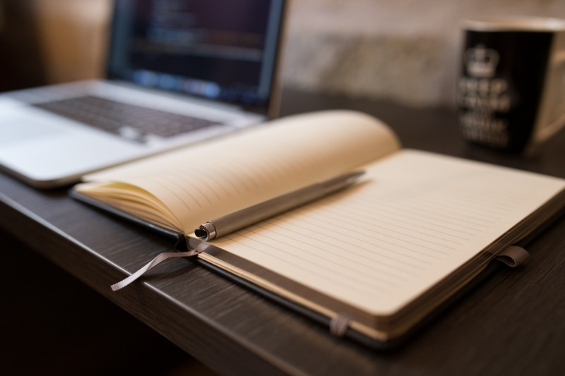 notebook-and-ballpoint-with-laptop-in-background
